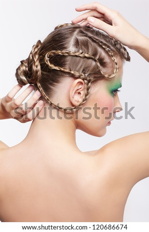 portrait of beautiful young dark blonde woman with creative braid hairdo and green eye shades make up touching her hair