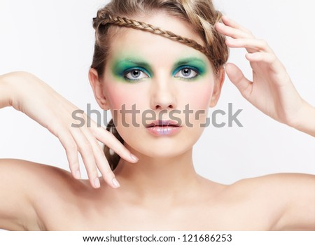 portrait of beautiful young dark blonde woman with creative braid hairdo and green eye shades make up posing on gray