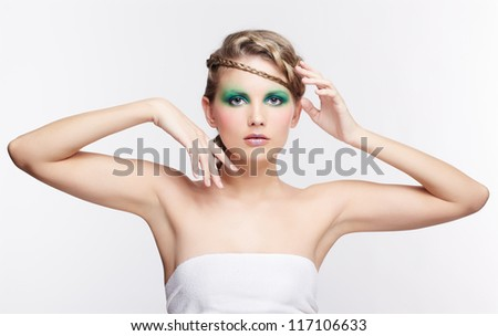 portrait of beautiful young dark blonde woman with creative braid hairdo posing on gray