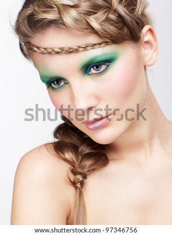 portrait of beautiful young dark blonde woman with creative braid hairdo posing on gray - stock photo