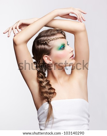 portrait of beautiful young dark blonde woman with creative braid hairdo posing on gray putting hands over her head - stock photo