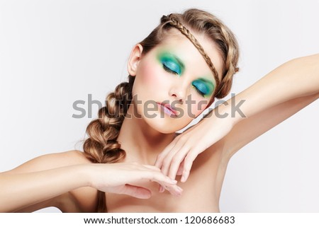 portrait of beautiful young dark blonde woman with creative braid hairdo posing on gray with eyes shut