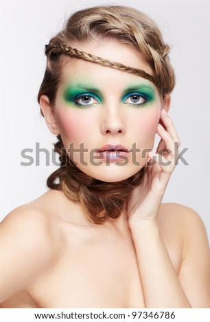 portrait of beautiful young dark blonde woman with creative braid hairdo touching face - stock photo