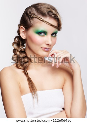 portrait of beautiful young dark blonde woman with creative braid hairdo touching her chin