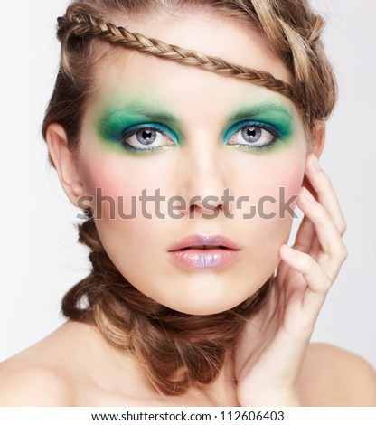 portrait of beautiful young dark blonde woman with creative braid hairdo touching her face
