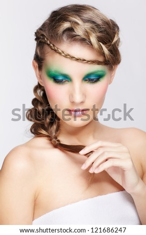 portrait of beautiful young dark blonde woman with creative braid hairdo touching her plait