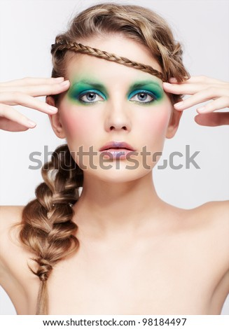 portrait of beautiful young dark blonde woman with creative braid hairdo touching temples
