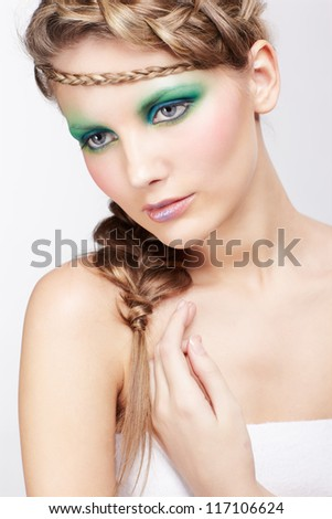 portrait of beautiful young dark blonde woman with creative plait coiffure posing on gray