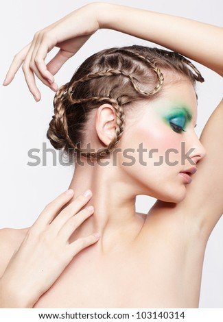 portrait of beautiful young dark blonde woman with creative plait hairdo and green eye shades touching her neck