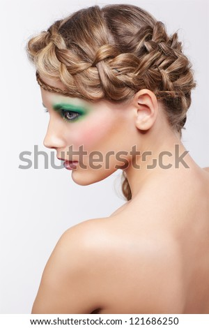 portrait of beautiful young dark blonde woman with creative plait hairdo and green eye shades make up on gray - stock photo
