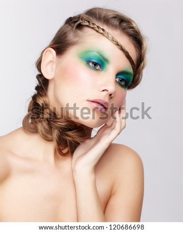 portrait of beautiful young dark blonde woman with creative plait hairdo touching face