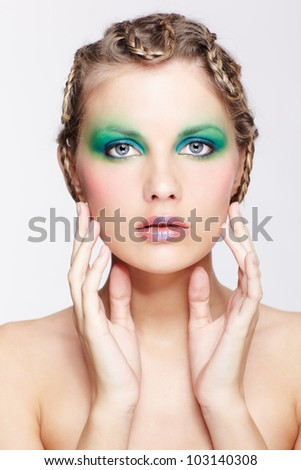 portrait of beautiful young dark blonde woman with creative plait hairdo touching her face