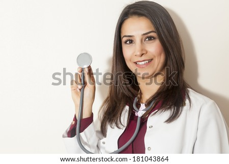 Portrait of beautiful young doctor holding a stethoscope - stock photo