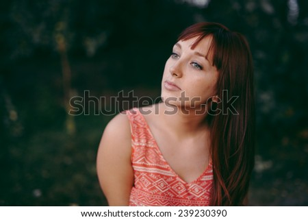 portrait of beautiful young female staring off into the sunset in a small grassy area head tilted - stock photo