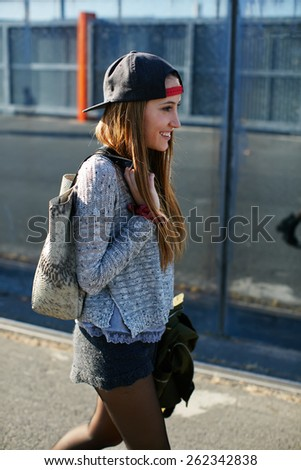 Portrait of beautiful young female walk on a street relaxing and enjoying sunny evening outdoors, shot of a young stylish teenager walking in the street looking into the distance and feeling so happy - stock photo