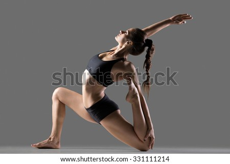Portrait of beautiful young fit woman doing sport exercises, variation of One Legged King Pigeon Posture - Eka Pada Rajakapotasana II, full length, side view, studio image on gray background - stock photo