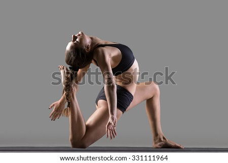 Portrait of beautiful young fit woman doing sport exercises, variation of One Legged King Pigeon Posture - Eka Pada Rajakapotasana II, full length, rear view, studio image on gray background - stock photo