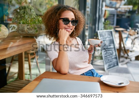 Portrait of beautiful young girl having a cup of coffee at cafe. Stylish young african girl drinking coffee at sidewalk cafe.