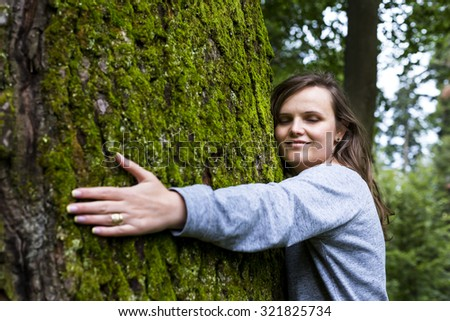 Portrait of beautiful young girl hugging a big tree in the forest  - stock photo