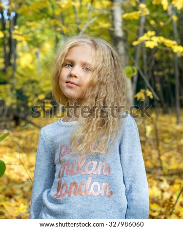 Portrait of beautiful young girl in autumn forest park - stock photo