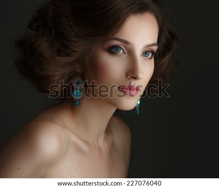 Portrait of beautiful young girl in earrings on a dark background. Studio photography.