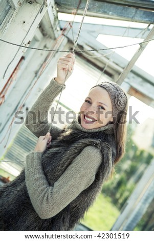 Portrait of beautiful young girl in glasshouse whose is hanging on small lines. Focus on face.