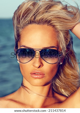 Portrait of beautiful young girl in sunglasses in the beach - stock photo