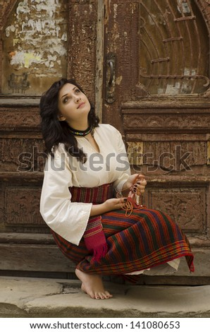 Portrait of beautiful young girl in traditional ukrainian cloth on old wood door background