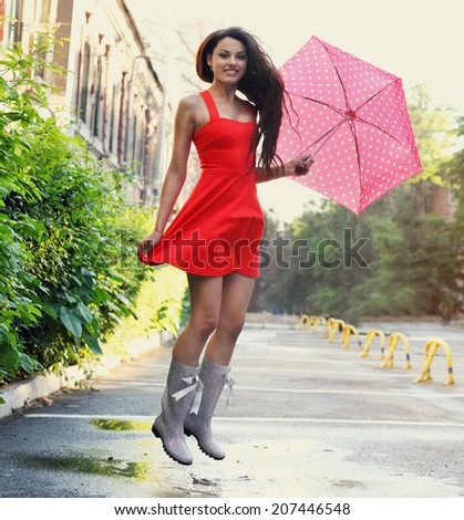 Portrait of beautiful young girl jumping with umbrella under rain - stock photo