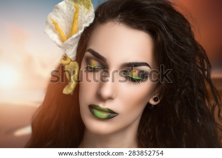 Portrait of beautiful young girl, lady, woman, model, actress, forest fairy, princess frog. Bright makeup, expressive eyes, green, yellow, eyeliner, arrows, colored lips, gradient,flower kala in hair - stock photo