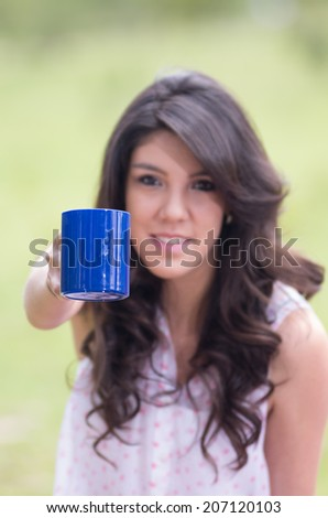 portrait of beautiful young girl offering a coffee in a field selective focus