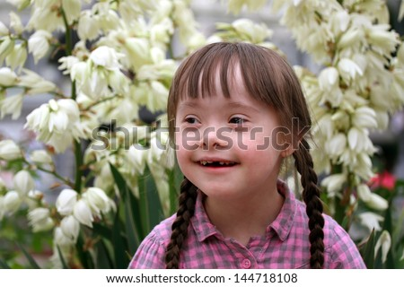 Portrait of beautiful young girl on flowers background - stock photo