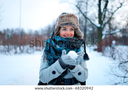 Portrait of beautiful young girl playing with snowball - stock photo