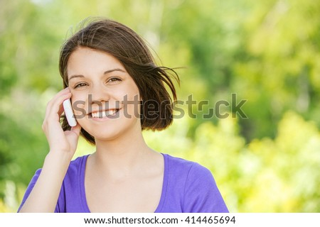 Portrait of beautiful young girl talking at the cell phone at summer green park - stock photo