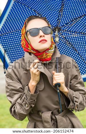 Portrait of beautiful young girl walking with umbrella under rain - stock photo