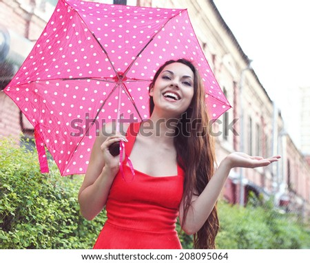 Portrait of beautiful young girl walking with umbrella under the rain - stock photo