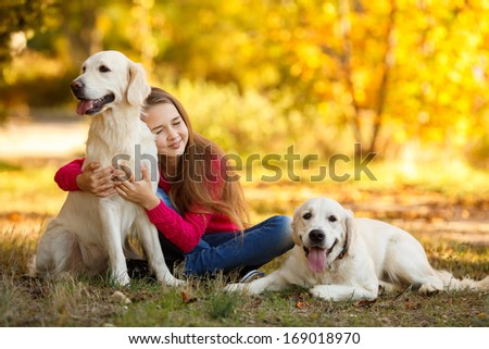 portrait of Beautiful young girl with her dogs labrador retrievers outdoor in autumn beautiful park - stock photo
