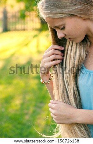 Portrait of beautiful young girl with long blond hair in blue dress in the countryside