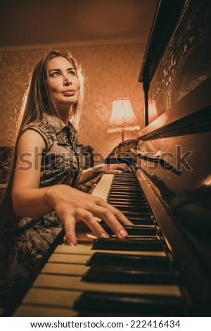 Portrait of beautiful young girl with long hair playing piano in interior. Musical instrument pianoforte with woman performer - stock photo