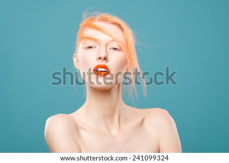 Portrait of beautiful young girl with orange hair on a blue background - stock photo
