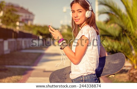 Portrait of beautiful young girl with skateboard and headphones listening music in her smartphone outdoors. Warm tones edition. - stock photo