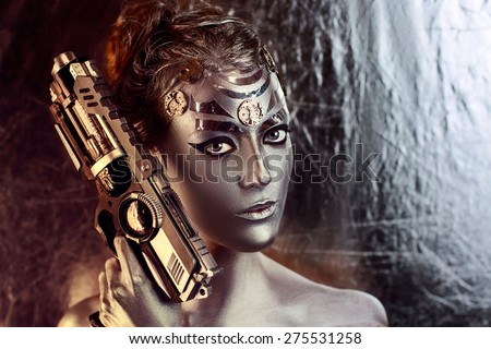 Portrait of beautiful young girl, woman, lady, hitman, killer, techno, future, progress. Ideal creative expressive makeup, silver skin, face, neck, shoulders, hand, arms. Stylish, bright, showy look.  - stock photo