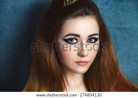 Portrait of beautiful young girl, woman, model, character, actress, fox, cat. Theater, fairy tale, party. Flawless makeup, expressive eyes, arrows, crystals, perfect skin, beige lips, gentle smile. - stock photo