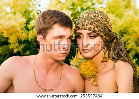 Portrait  of beautiful  young happy couple   in spring blossom garden. - stock photo