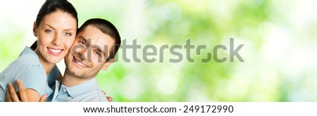 Portrait of beautiful young happy couple outdoor, with copyspace - stock photo