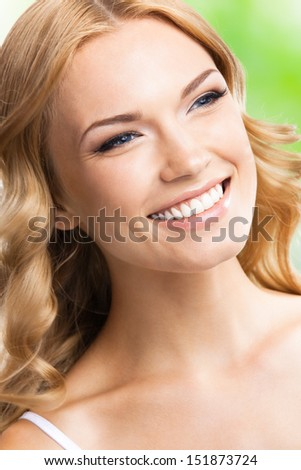 Portrait of beautiful young happy smiling blond woman with long hair, outdoors - stock photo