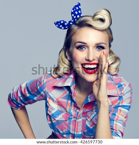 Portrait of beautiful young happy smiling woman, dressed in pin-up style. Caucasian blond model posing in retro fashion and vintage concept studio shoot. - stock photo