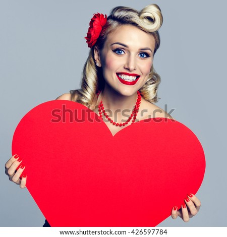 Portrait of beautiful young happy smiling woman holding heart symbol, dressed in pin-up style. Caucasian blond model posing in retro fashion and vintage concept studio shoot. - stock photo