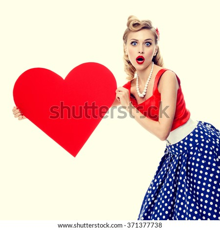 portrait of beautiful young happy smiling woman holding heart symbol, dressed in pin-up style dress with polka dot. Caucasian blond model posing in retro fashion and vintage concept studio shoot.