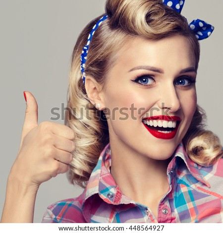 Portrait of beautiful young happy smiling woman, showing thumb up gesture, dressed in pin-up style. Caucasian blond model posing in retro fashion and vintage concept studio shoot.